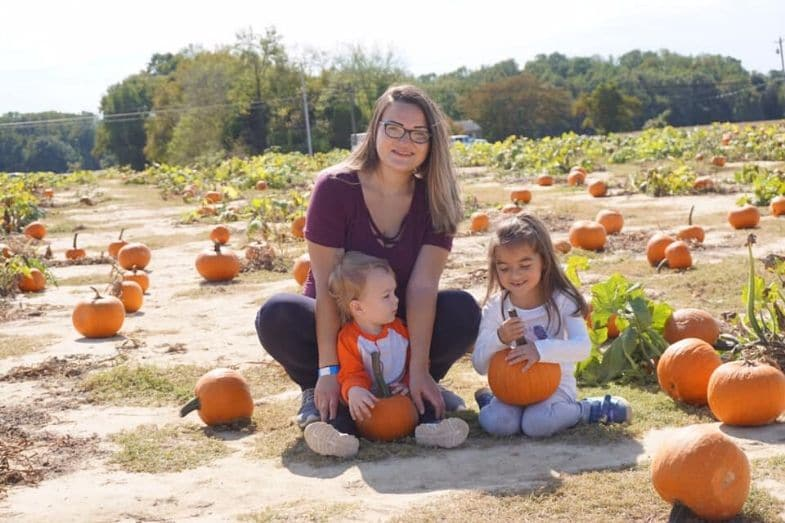 Emma and two of her children pose for a picture in a pumpkin patch.
