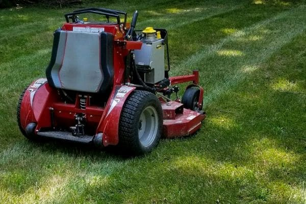 Professional grade lawn mower parked in a lush green yard.