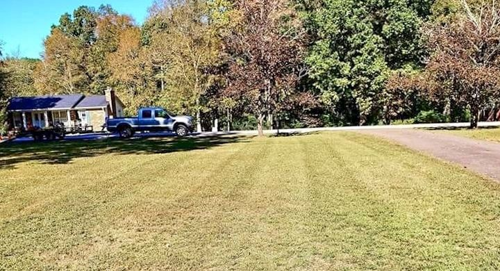 A Freshly Mowed lawn with Truck and Equipment in the backround