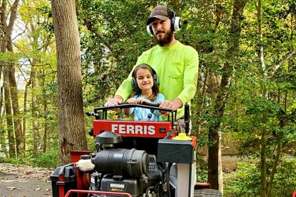 Father and Daughter on a Red Mower