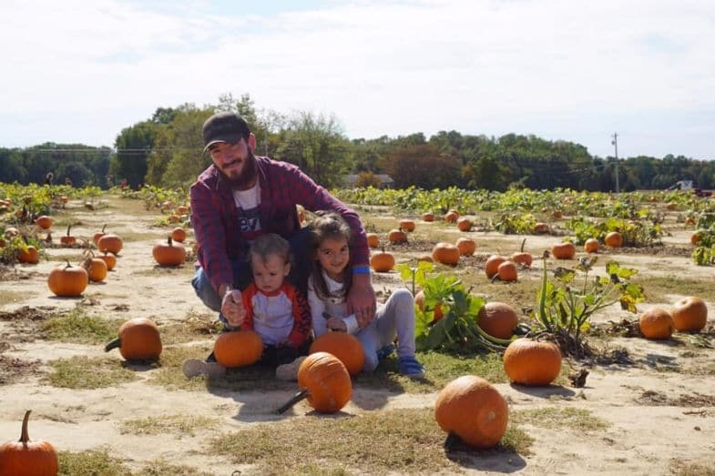 Gary and two of his children pose for a picture in a pumpkin patch.